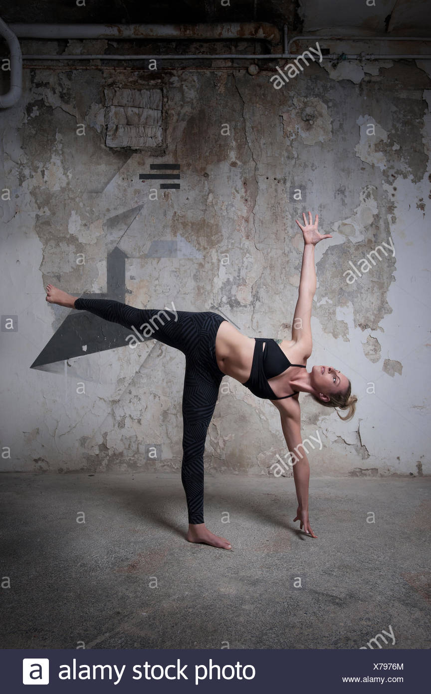 Mid adult woman practicing half moon pose in yoga studio, Munich, Bavaria, Germany - Stock Image
