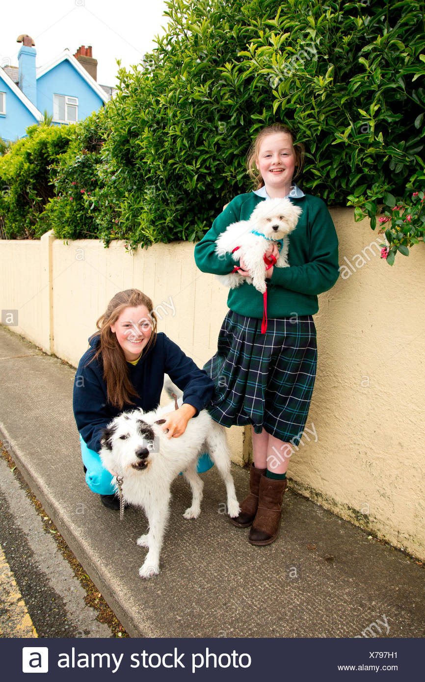 Two schoolgirls and their dogs stop for a moment on The Strand in Sandycove outside central Dublin. - Stock Image