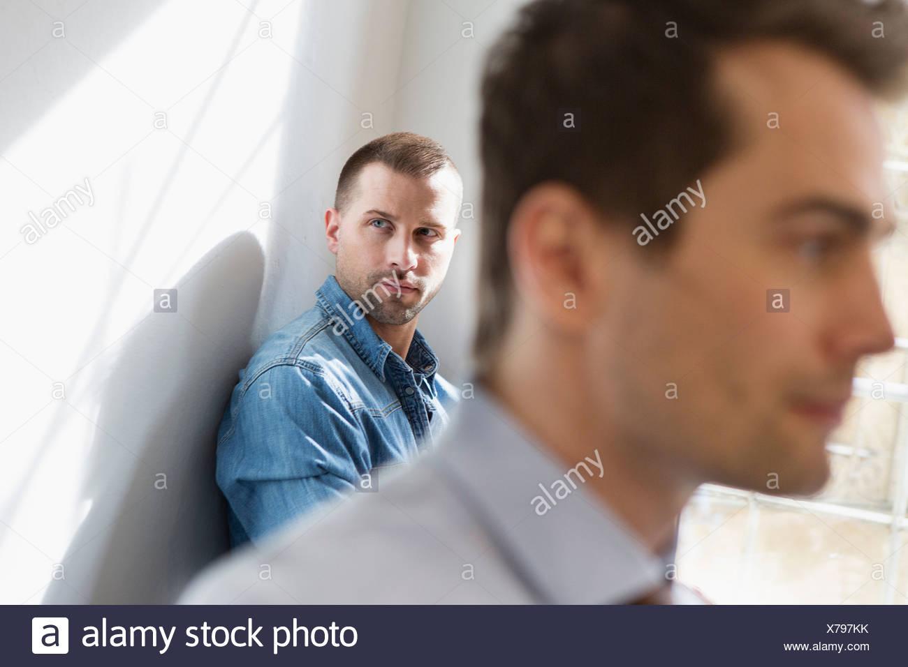 Mid adult man wearing denim shirt, man in foreground - Stock Image