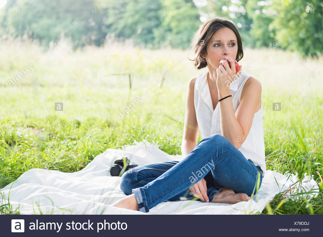Mid adult woman sitting on picnic blanket in field eating an apple Stock Photo