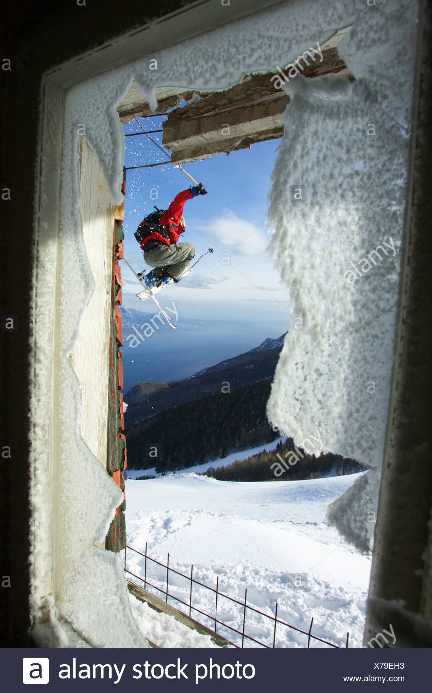 Skier jumping in front of a broken window - Stock Image