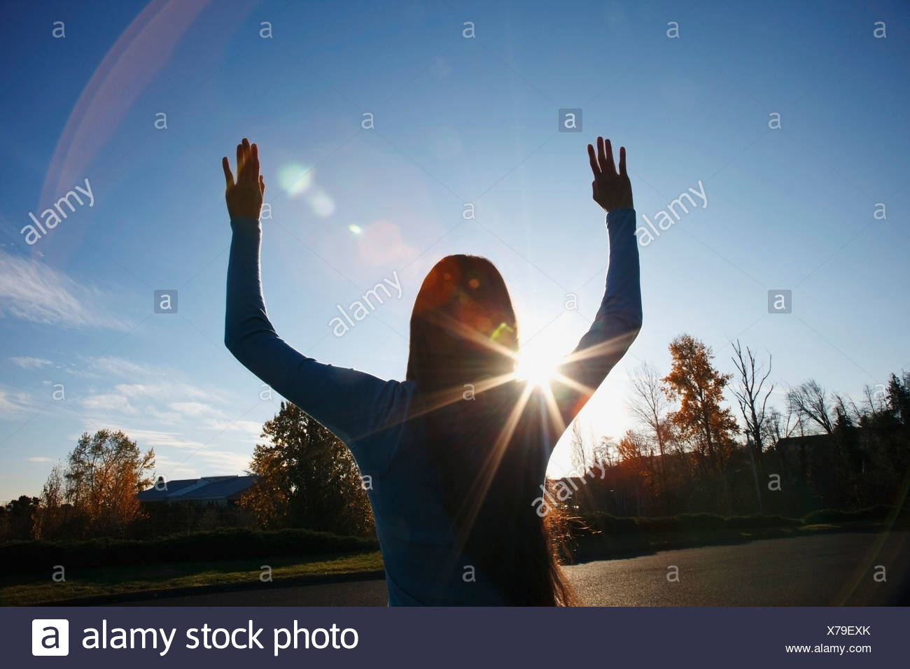 Beams Of Sunlight And A Circular Glare Around A Teenage Girl With Her Hands Raised - Stock Image