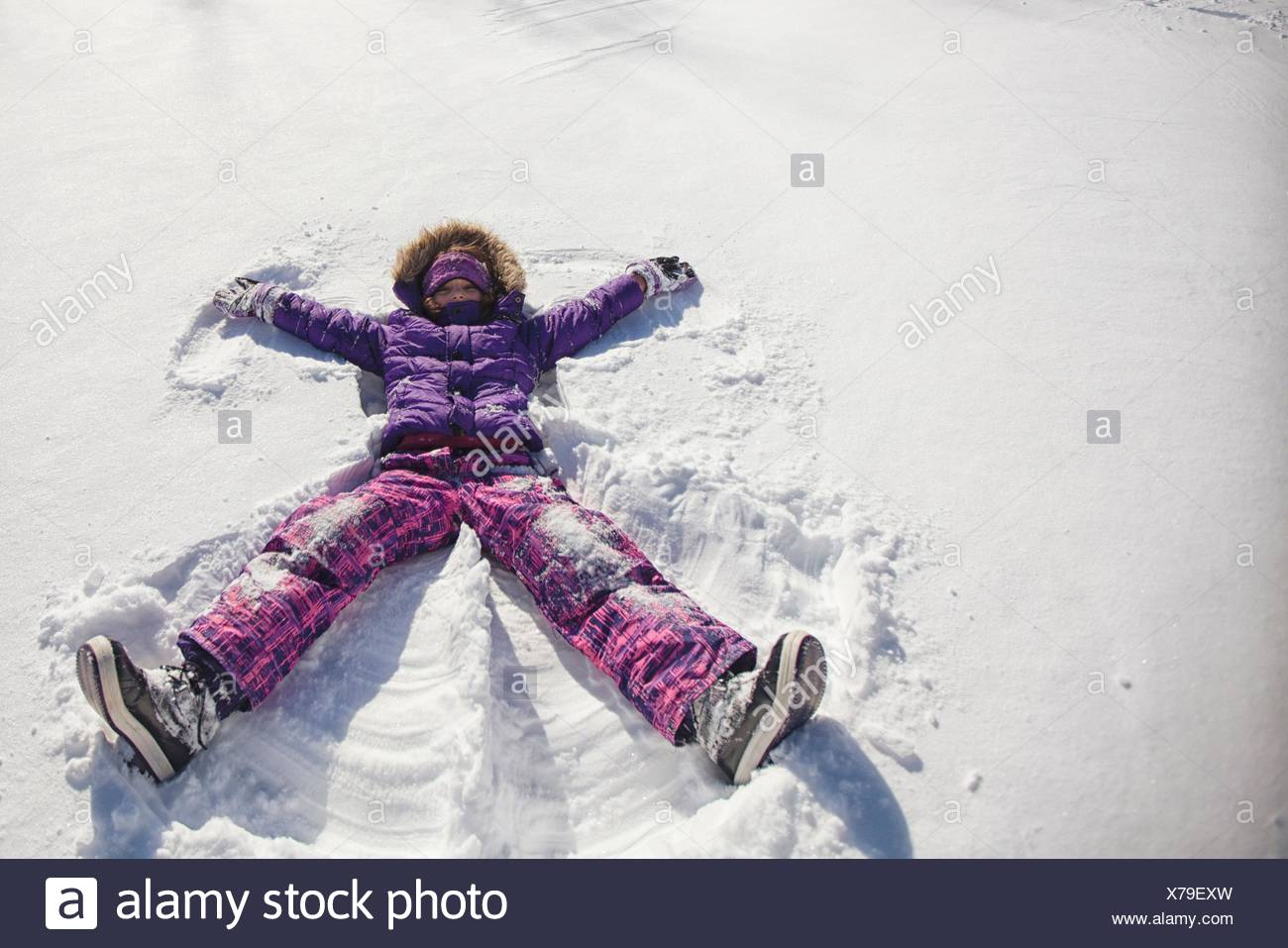 High angle view of girl wearing ski suit lying snow making snow angel - Stock Image