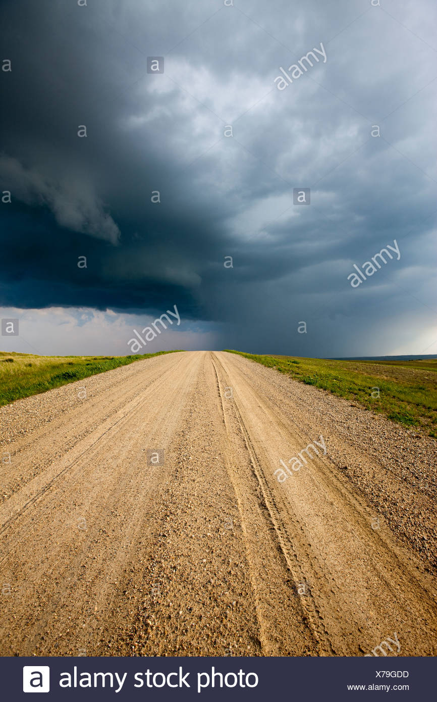 Storm clouds over a dirt road through the prairies, Saskatchewan, Canada. - Stock Image