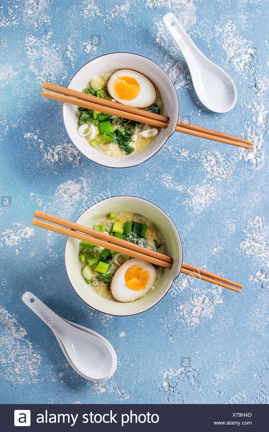 Two bowls with asian style soup with scrambled eggs, half of marinated egg, spring onion, spinach served with wood chopsticks and spoons over blue tex - Stock Image