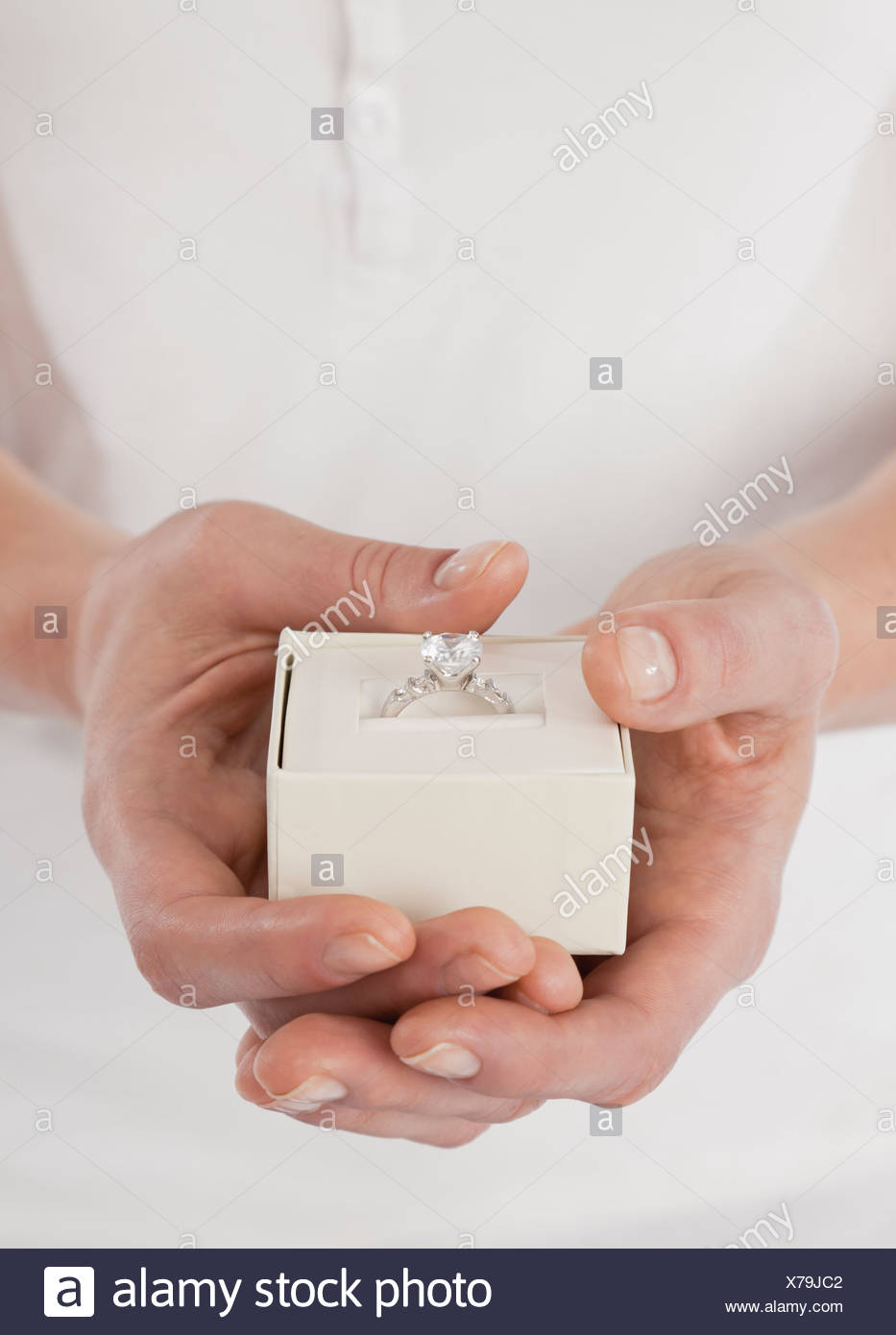 Close-up of woman's hands holding diamond ring in box - Stock Image