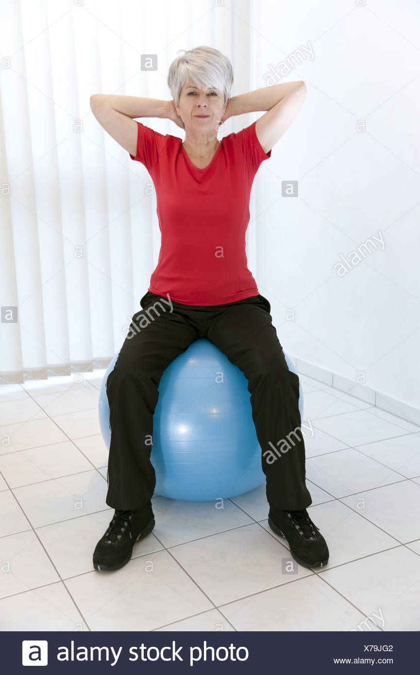 Woman, 50 +, sitting on a stability ball - Stock Image
