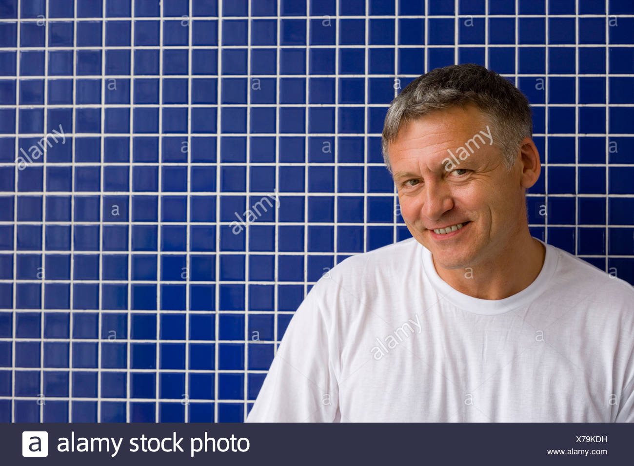 Mature man by tiles on wall, smiling, portrait, close-up - Stock Image