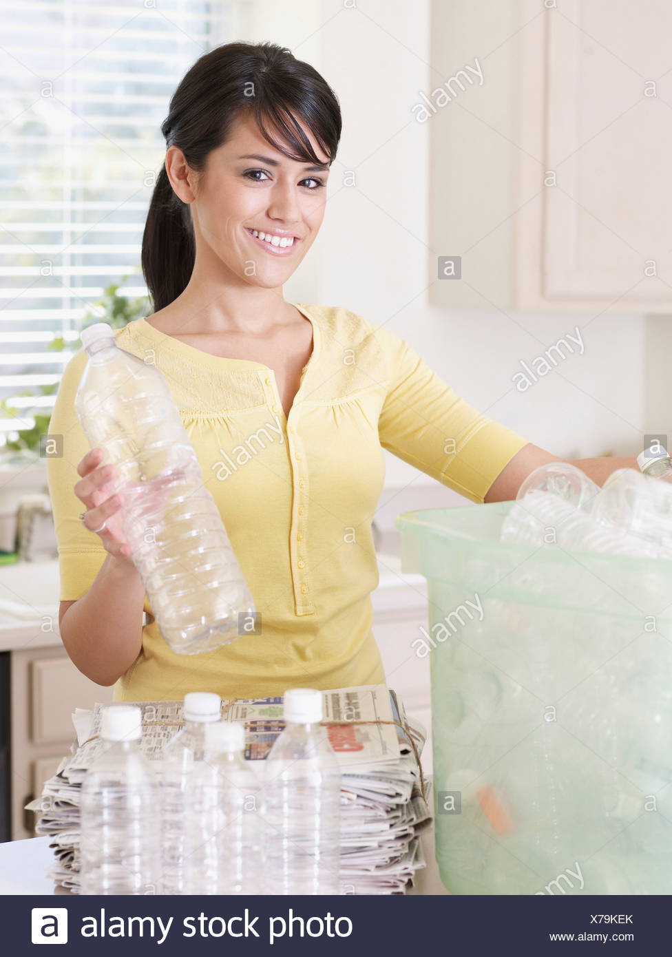 Woman in kitchen with recyclable materials and bin smiling - Stock Image