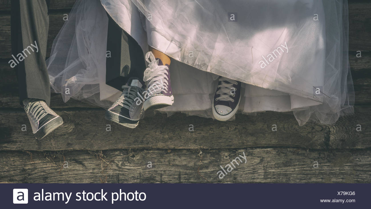 Low-section of newlyweds in canvas shoes - Stock Image