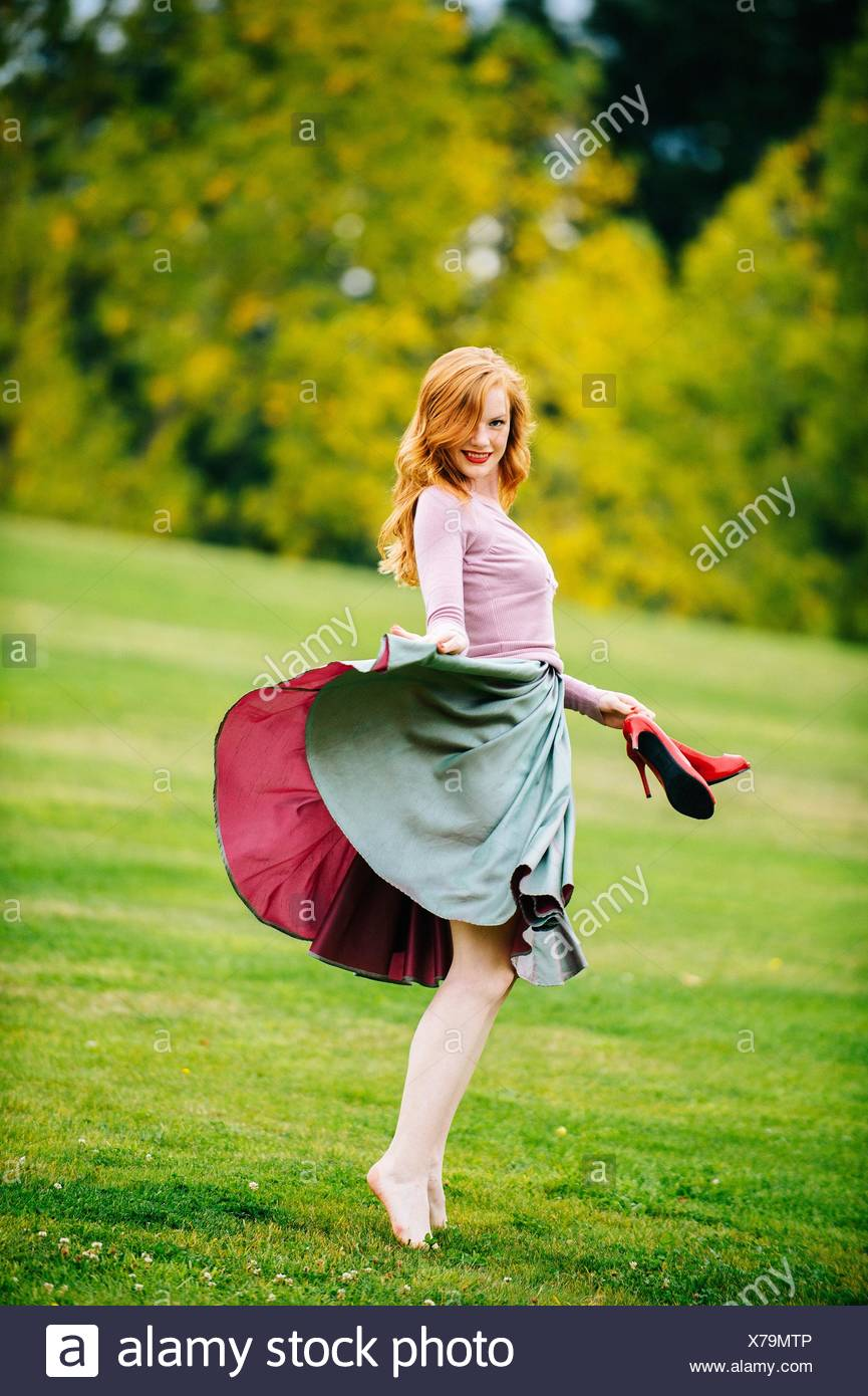 Portrait of young female dancer poised holding skirt and red high heels in park - Stock Image