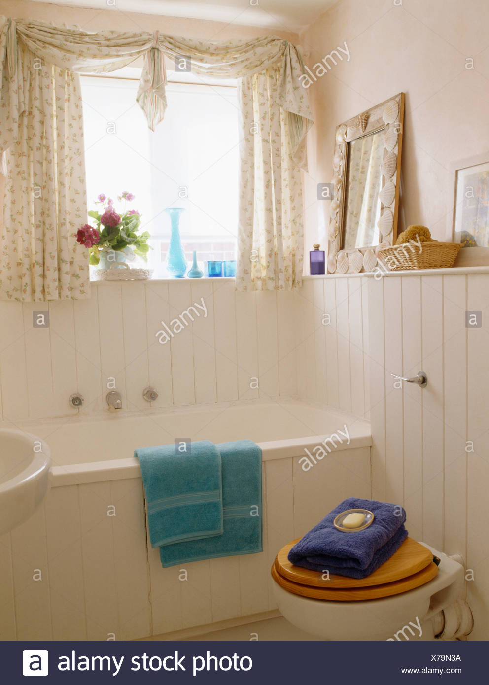Pale Pink Bathroom With White Tongue Groove Panelling And Pink Floral Curtains On Window Above Bath Stock Photo Alamy