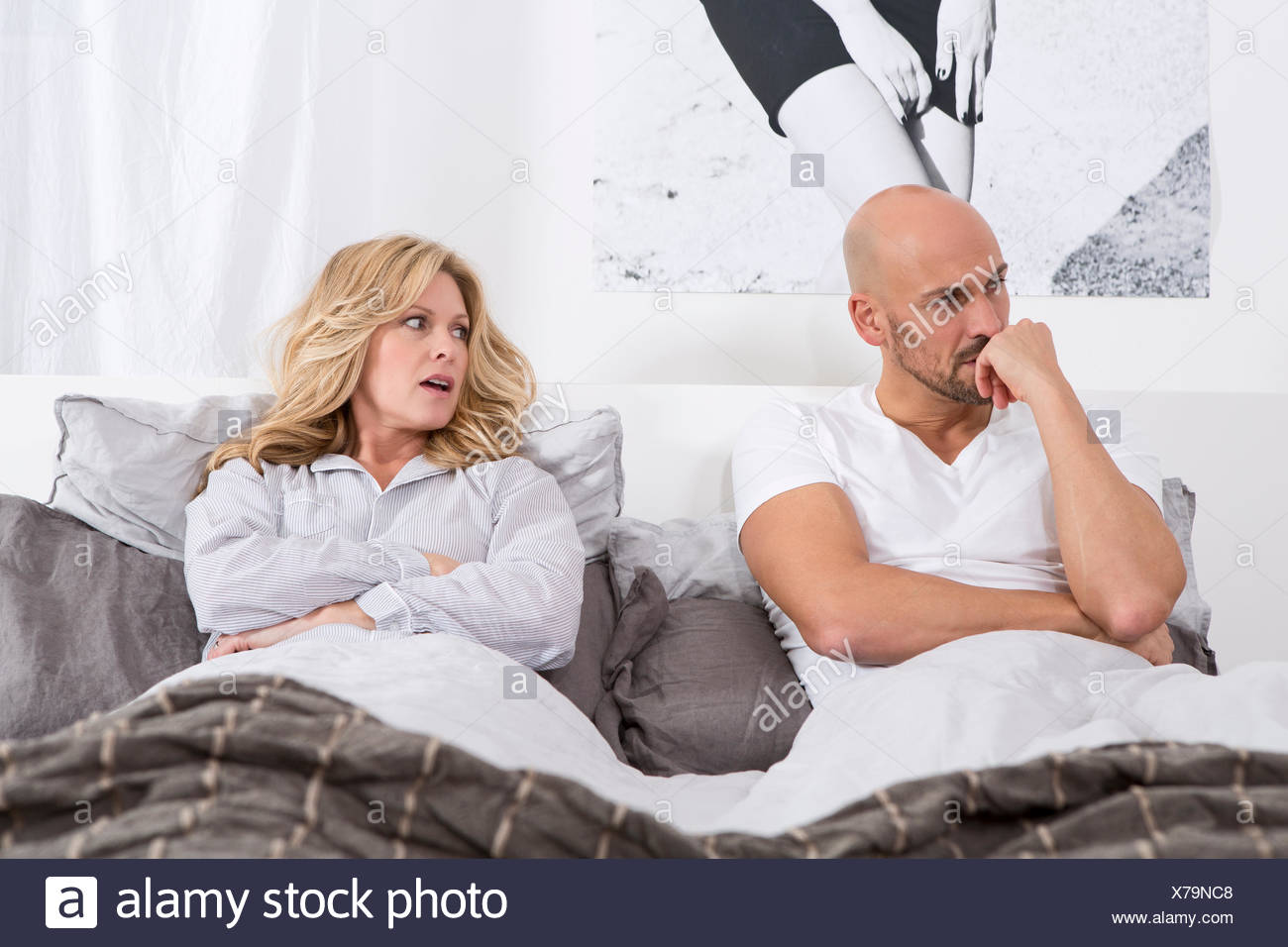 Mature couple lying in bed having relationship problems - Stock Image