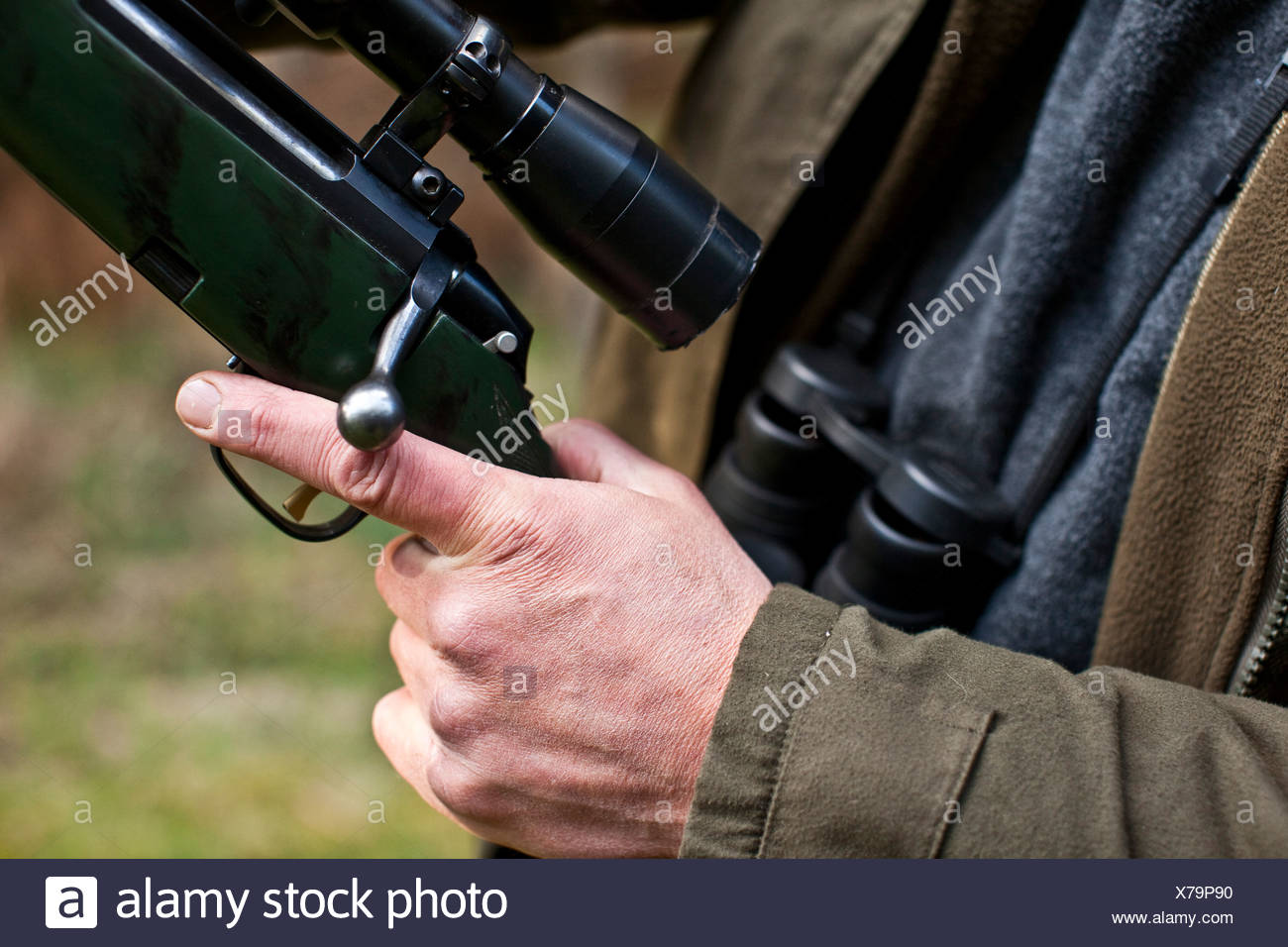 Man with his finger on the trigger of a gun, deer hunting in Thetford forest, UK - Stock Image