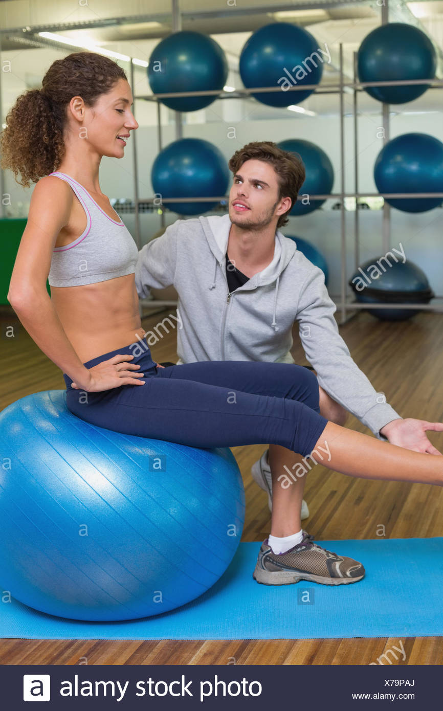 Trainer watching his client lift leg on exercise ball - Stock Image