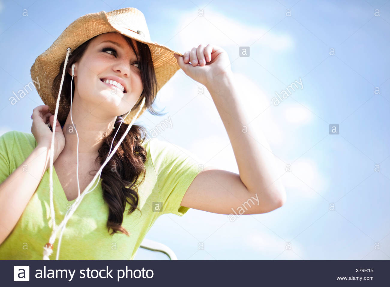 A young woman looks off while smiling listening to music. - Stock Image