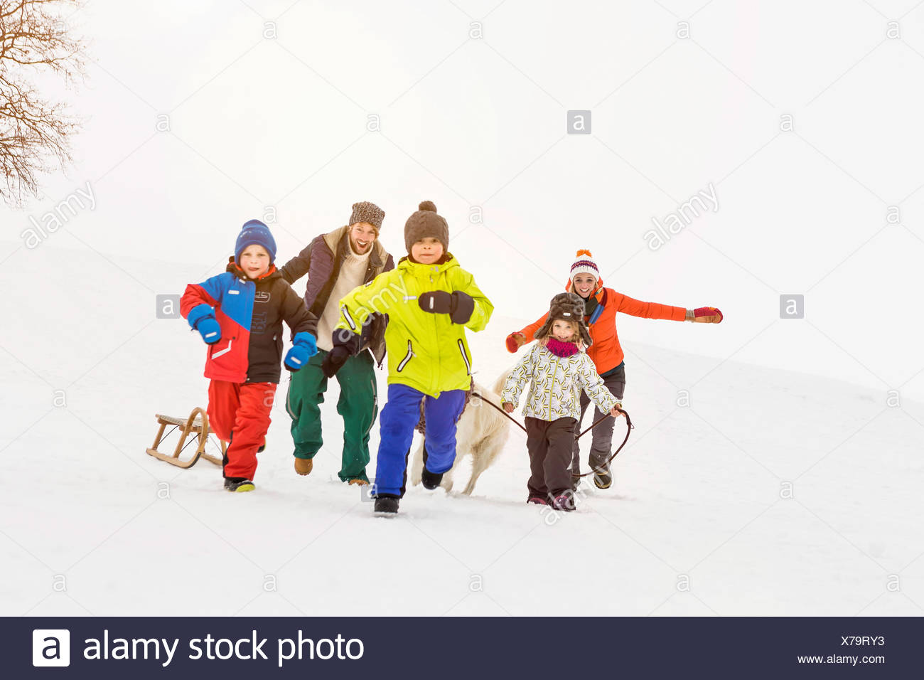 Family with three children running in snow - Stock Image