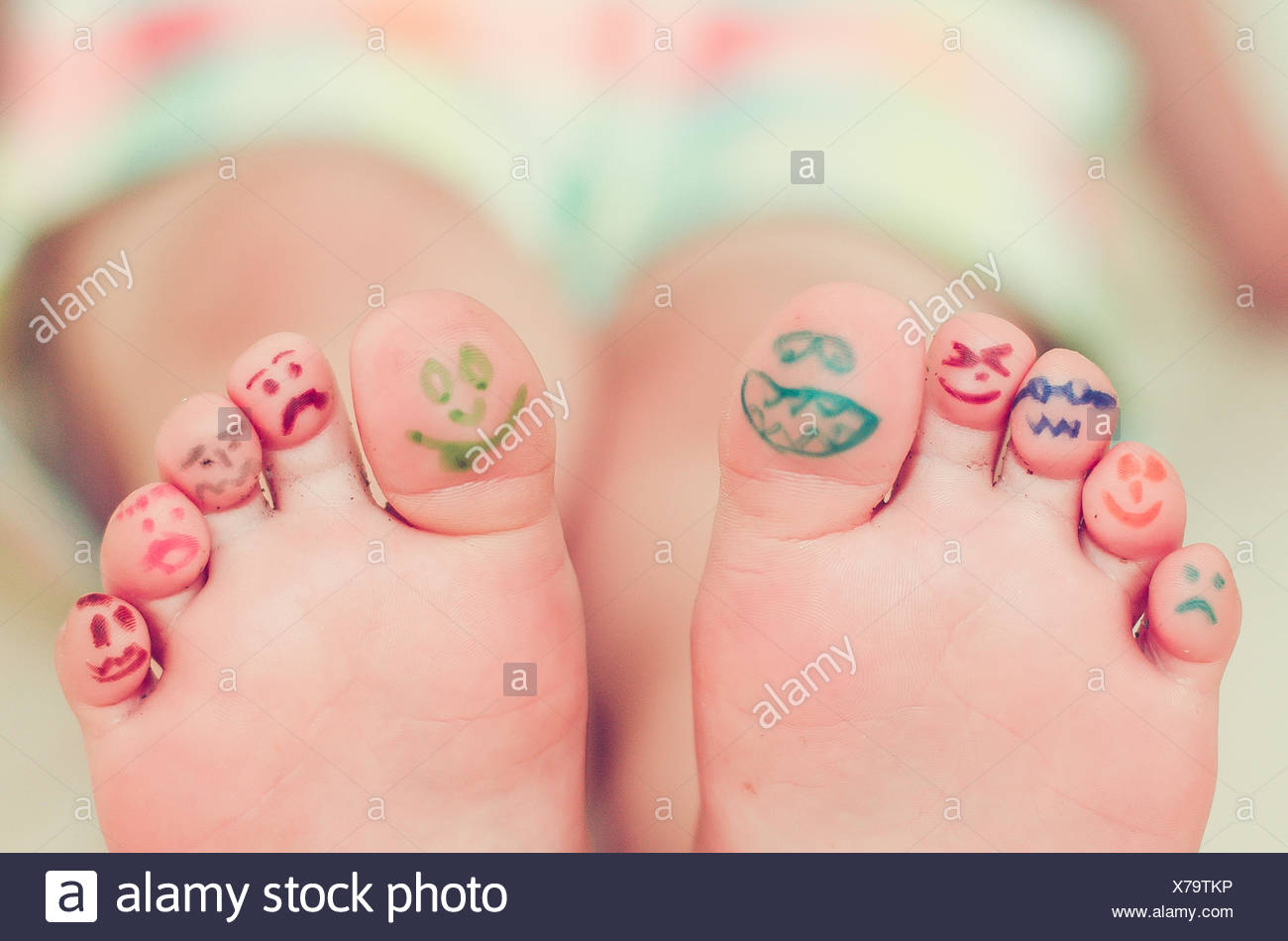 Girls feet with smiley face drawings - Stock Image