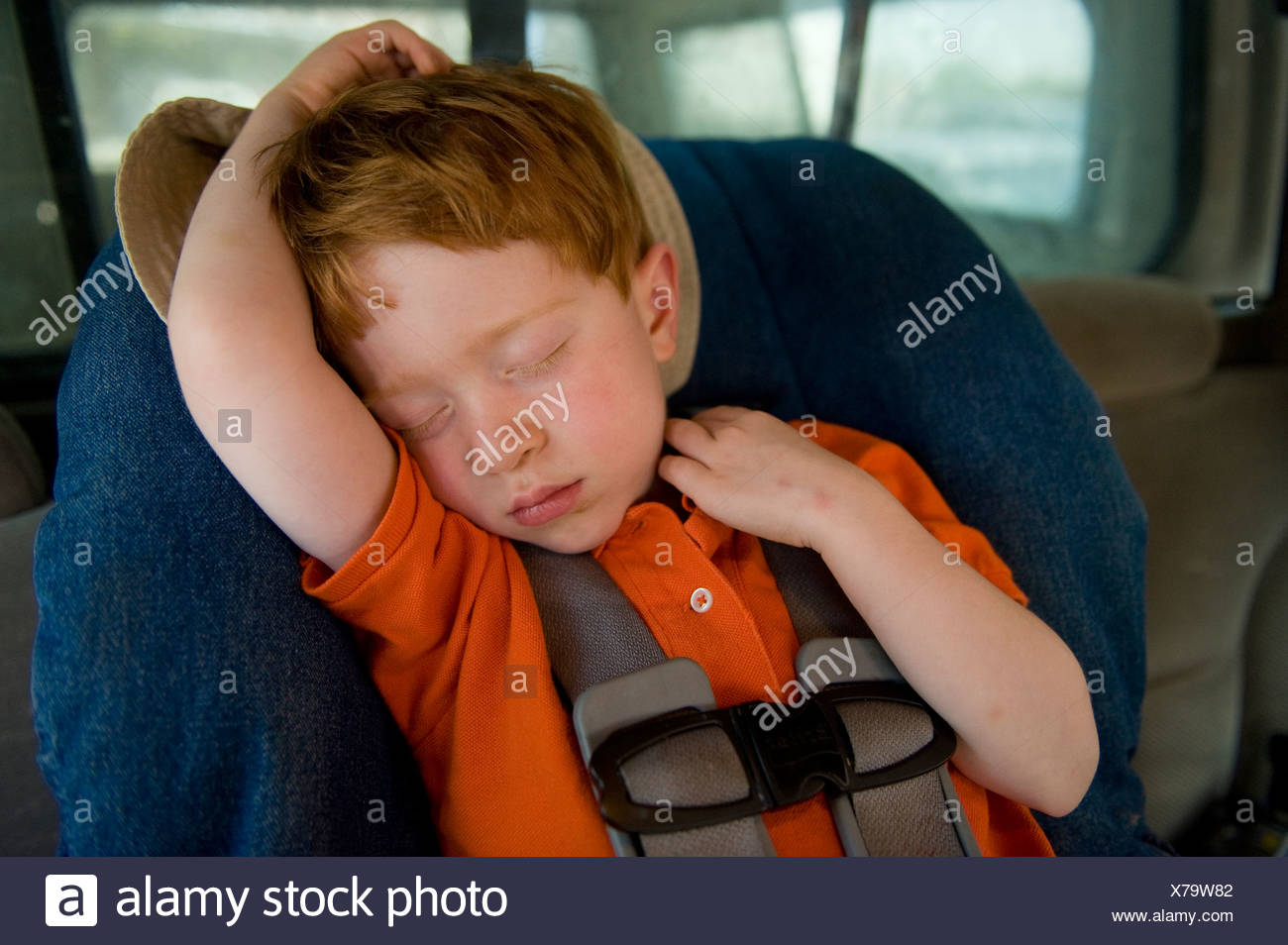 A young boy takes a nap in his car seat. - Stock Image