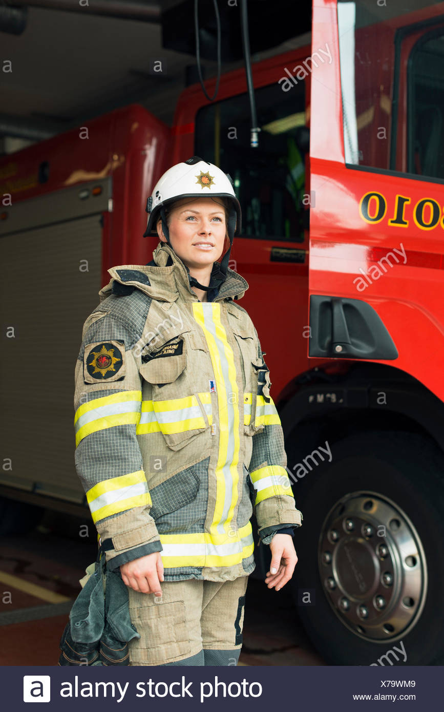 Sweden, Smiling female firefighter by fire engine - Stock Image