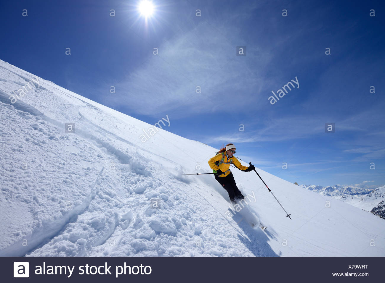 Female backcountry skier downhill skiing, Vallatscha, Sesvenna range, Ofenpass, Grisons, Switzerland - Stock Image