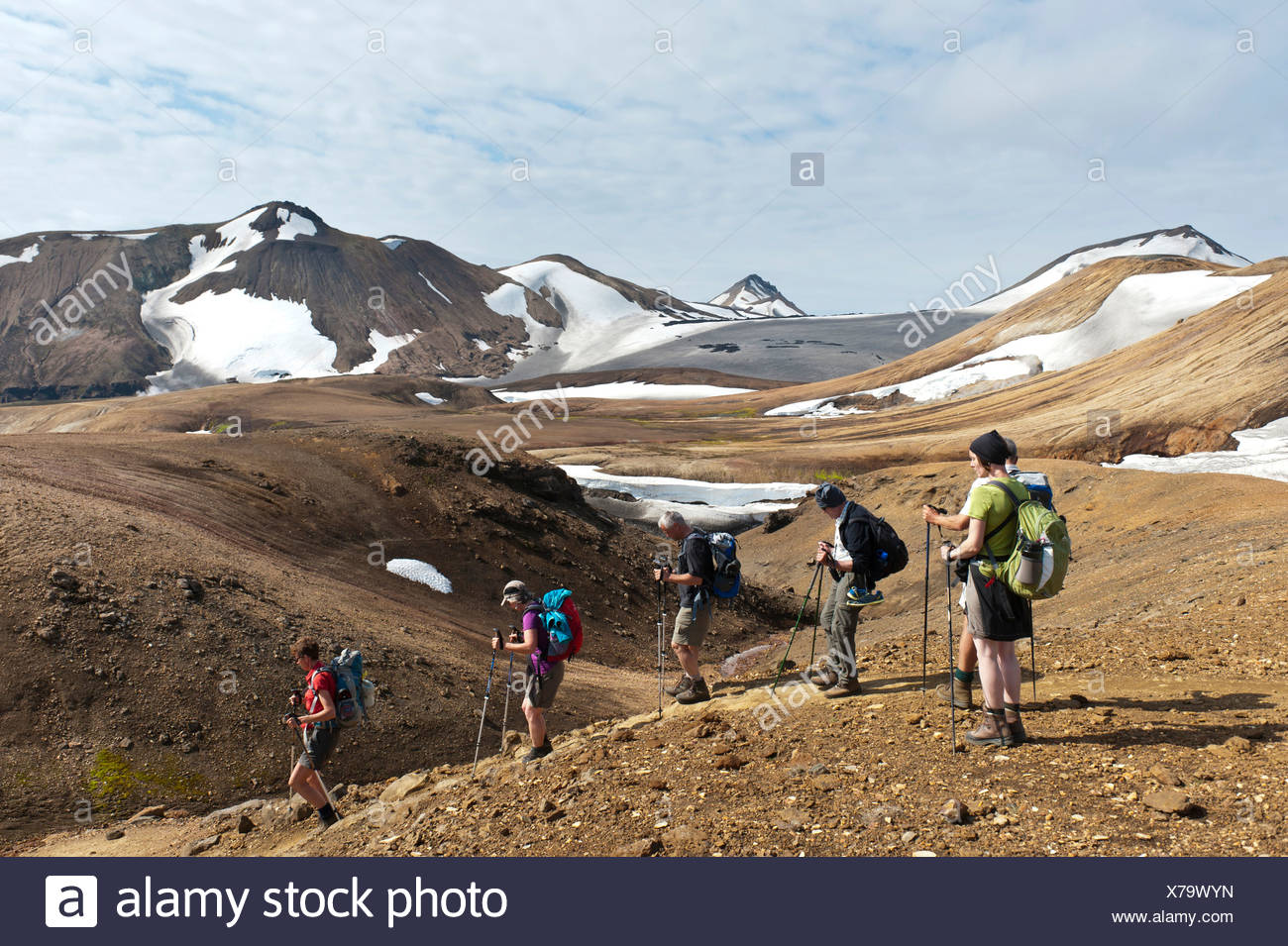 Trekking in the highlands, hiking group travelling downhill in single file, mountain landscape, glaciers and snowfields - Stock Image