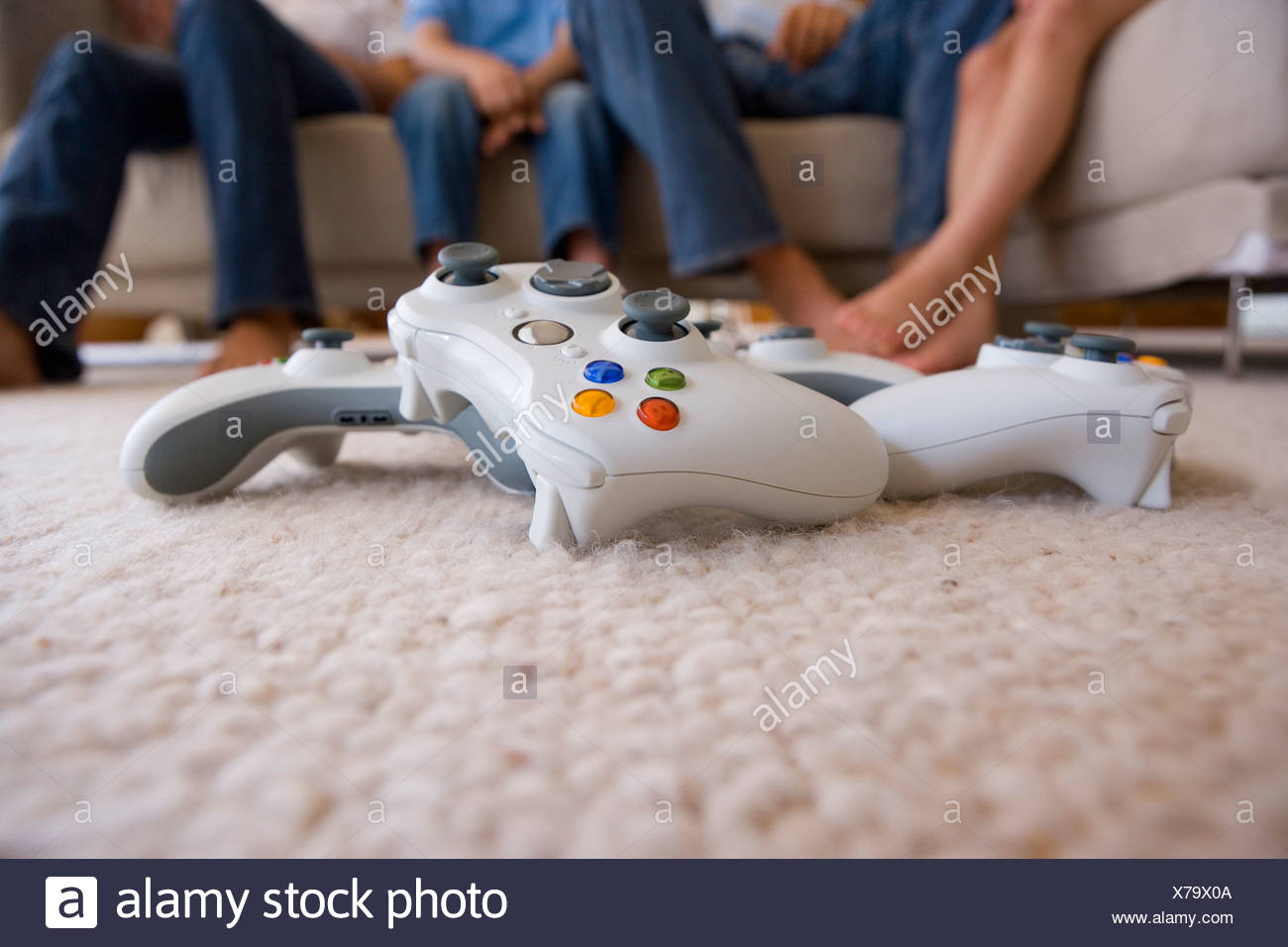 Close up of video game controller on living room floor - Stock Image