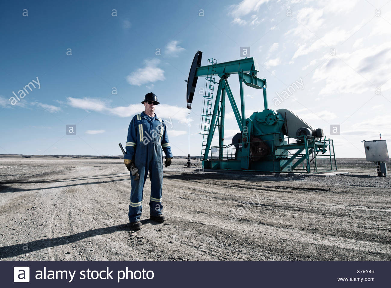 A man in overalls and a hard hat with a large wrench working at an oil extraction site. - Stock Image