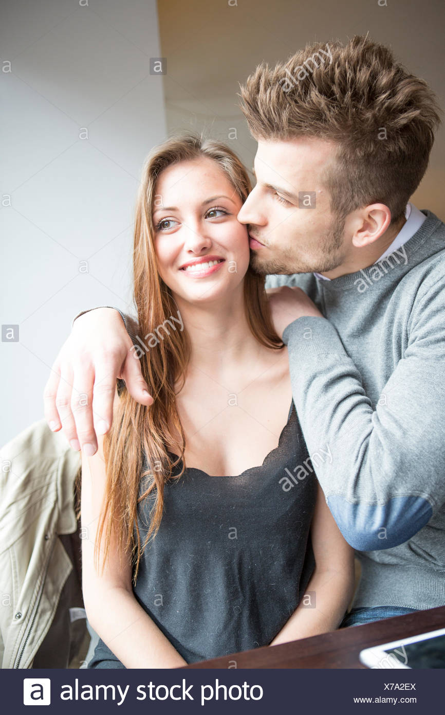Romantic young man kissing woman in cafe - Stock Image