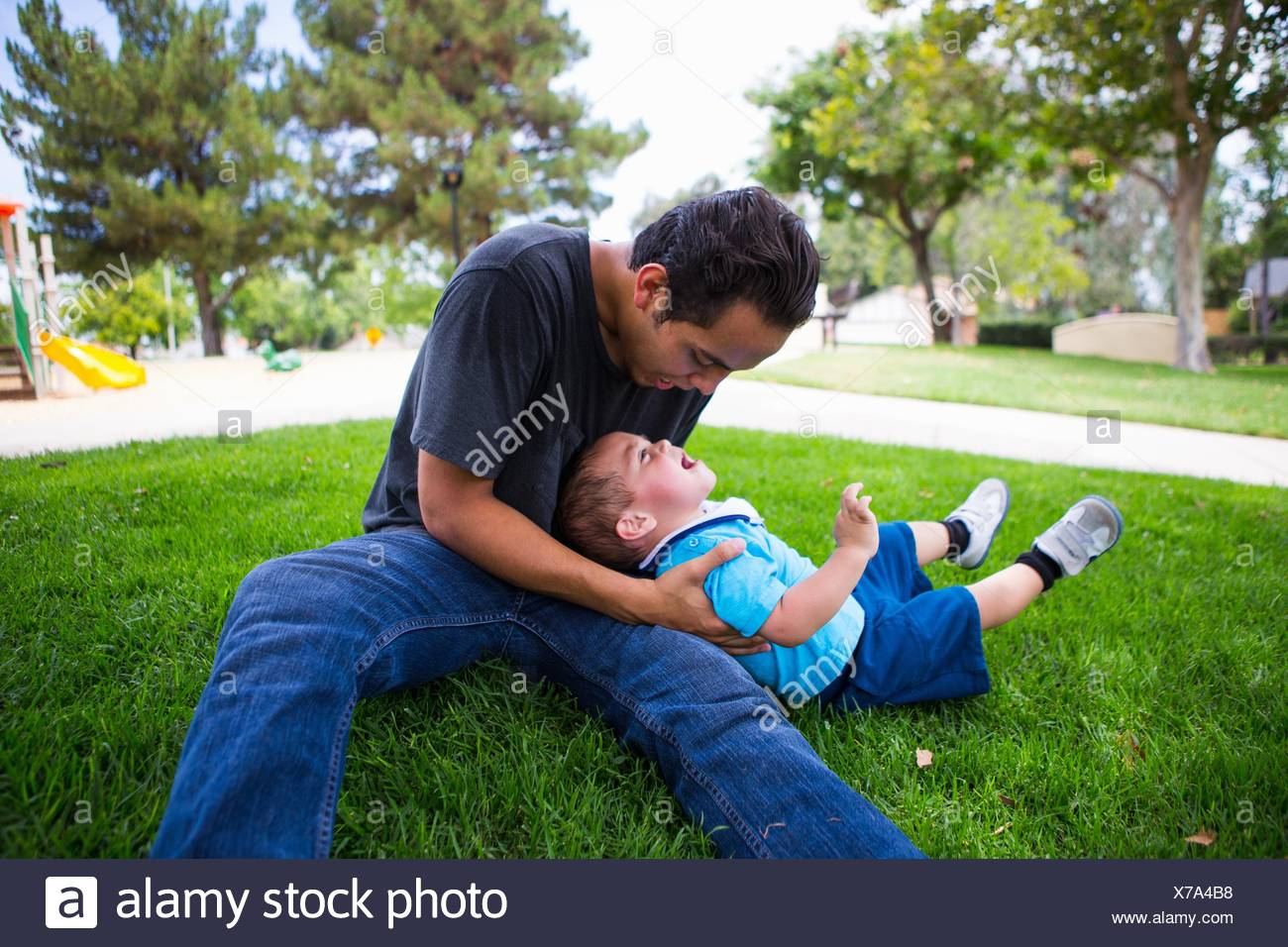 Male toddler playing with older adult brother in park - Stock Image