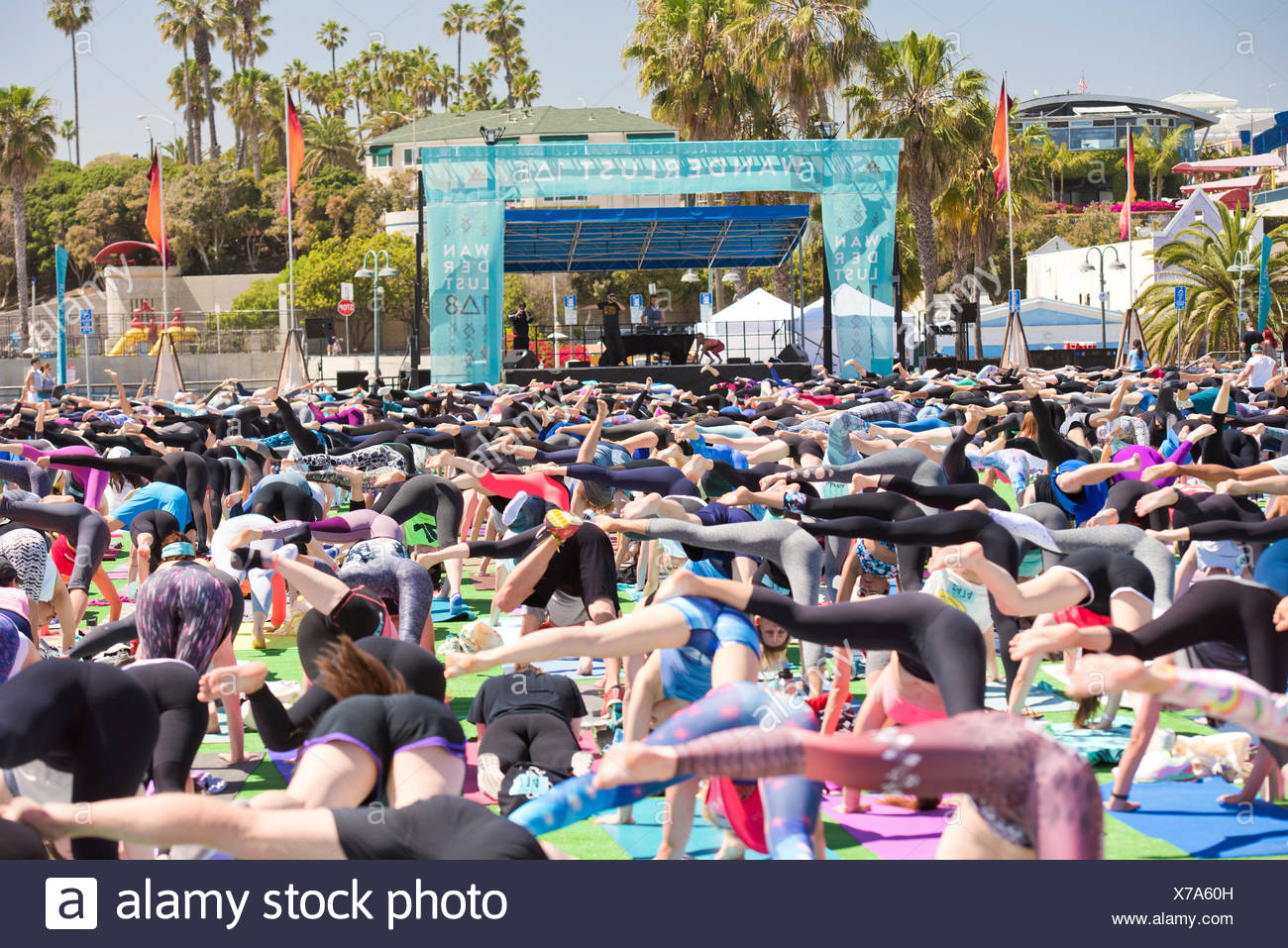 People doing one legged downward dog pose during outdoor yoga festival on Santa Monica Pier in Santa Monica, California, USA - Stock Image