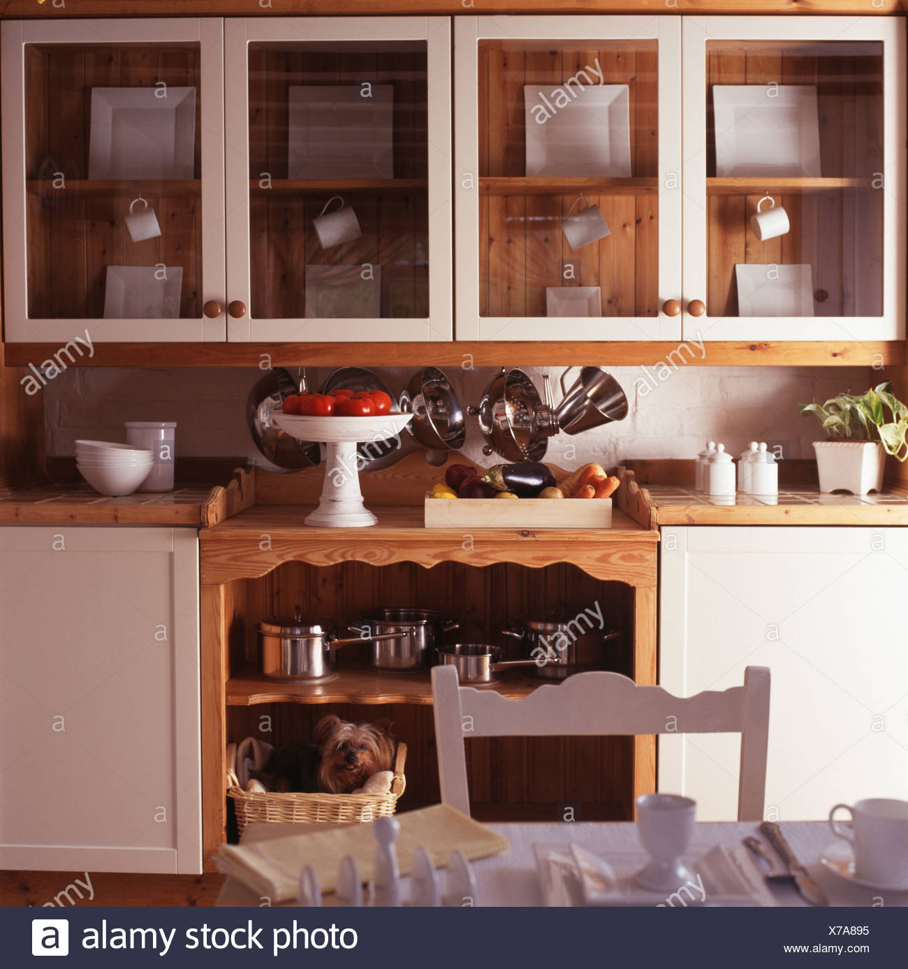 Fitted Cupboards With Glazed Doors Above Cream Cupboards And Wooden Shelves In Cream Cottage Kitchen Stock Photo Alamy