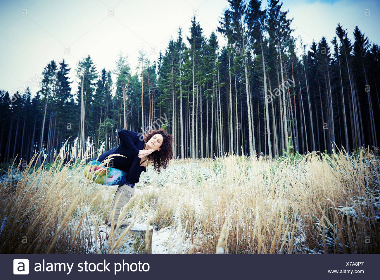 Mid adult woman practicing yoga moves in forest - Stock Image