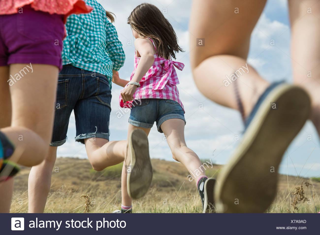 Rear view of schoolgirls running - Stock Image