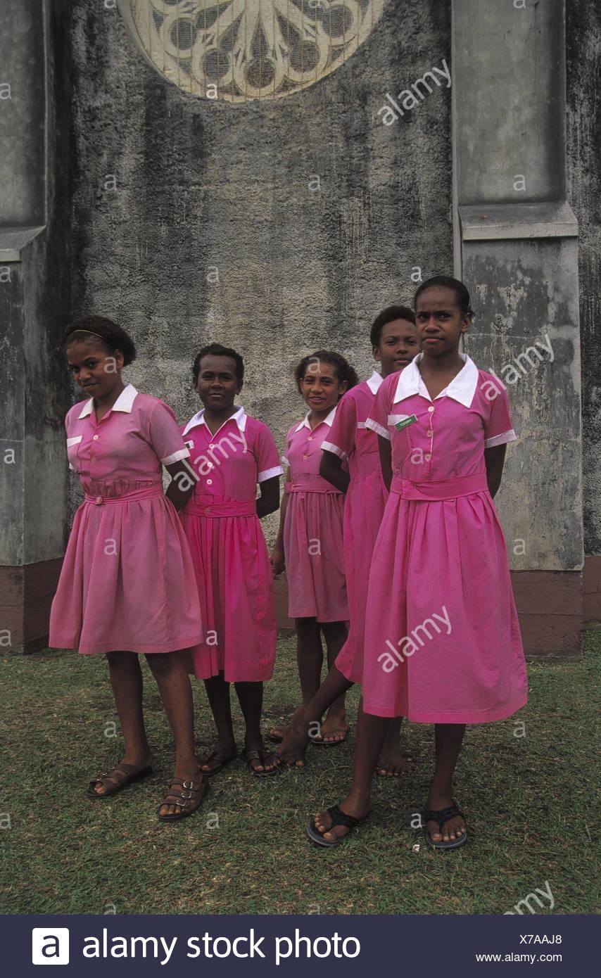 Fidschi Inseln, Insel Ovalau, Levuka,  Gebäude, Schülerinnen, Gruppenbild  Südsee, Schule, Kinder, Mädchen, Teenager, Einheimische, Schulkleidung, Kleider, rosa, einheitlich, Freundinnen, Ganzkörper, außen - Stock Image