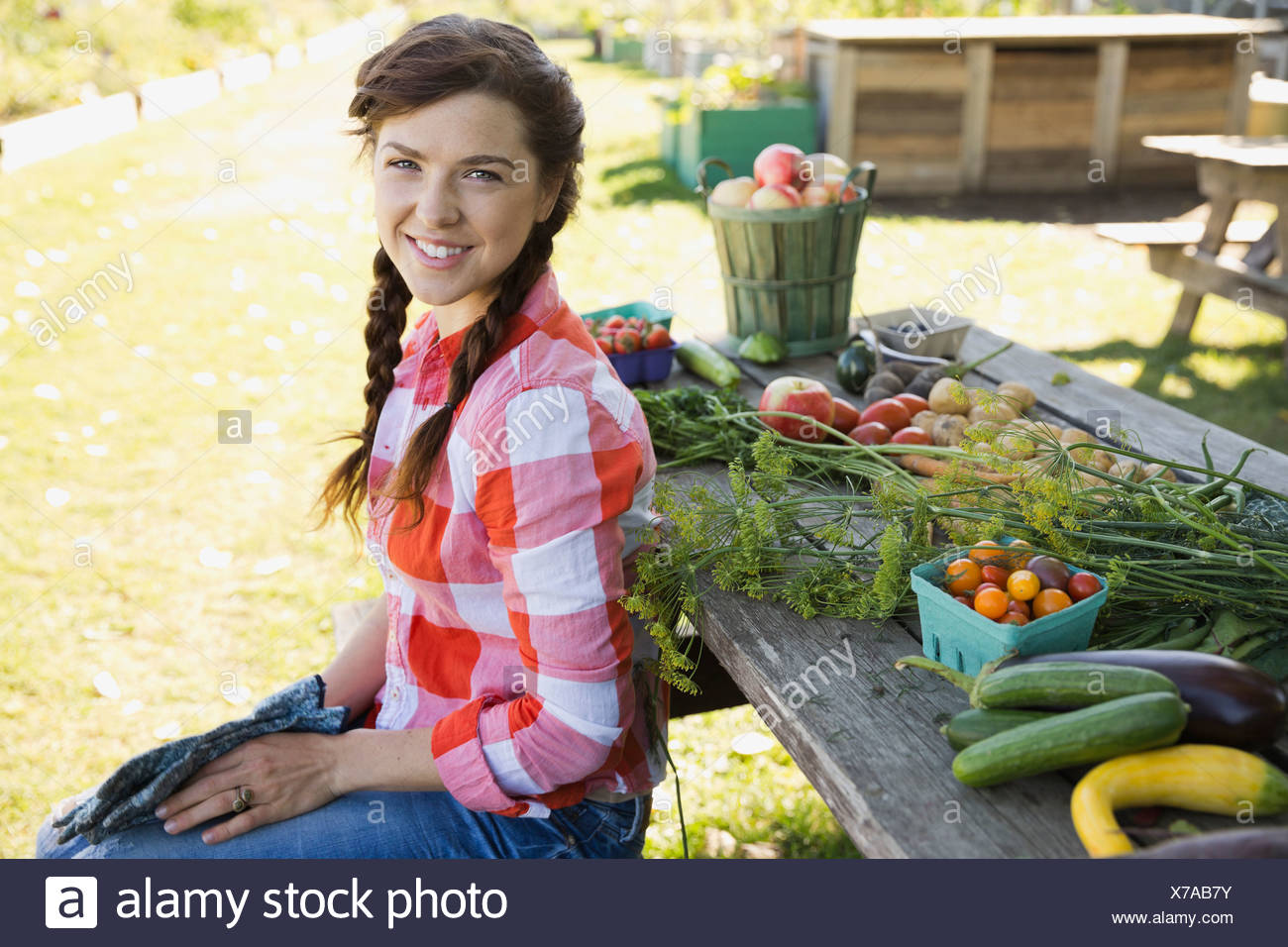 Woman sitting next to harvested fruit and vegetables - Stock Image