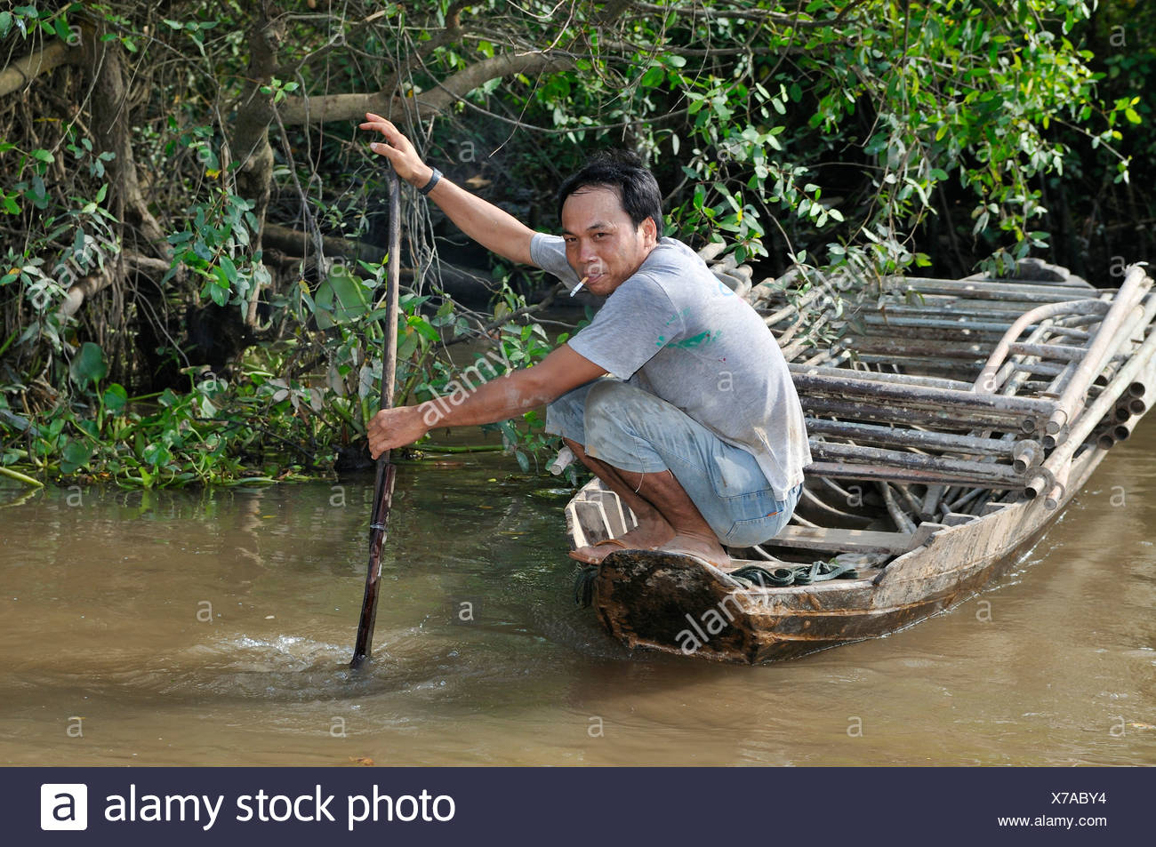 Man rowing a wooden boat, Mekong Delta, Vietnam, Asia - Stock Image