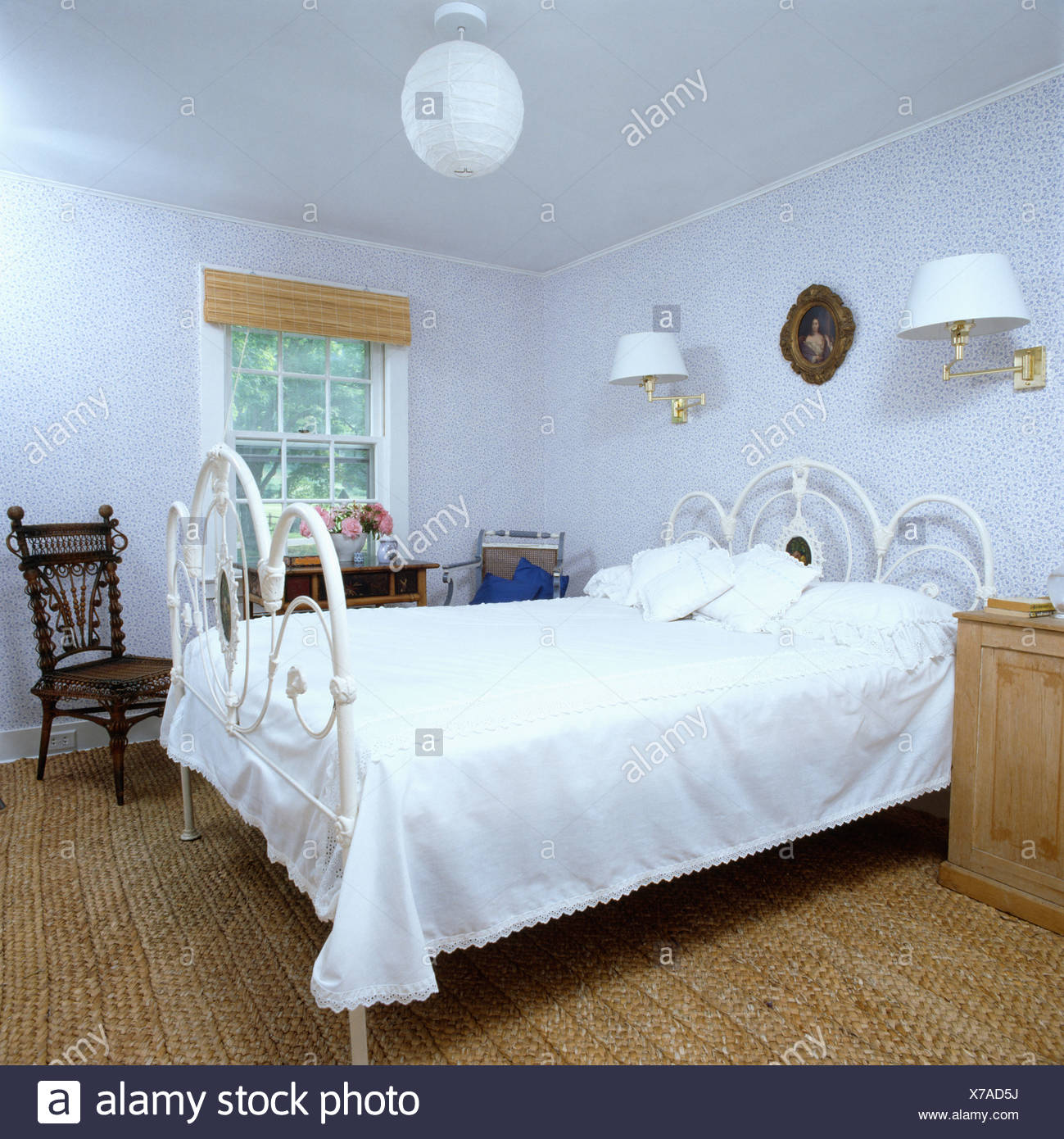 White wrought-iron bed in white country bedroom with seagrass carpet ...