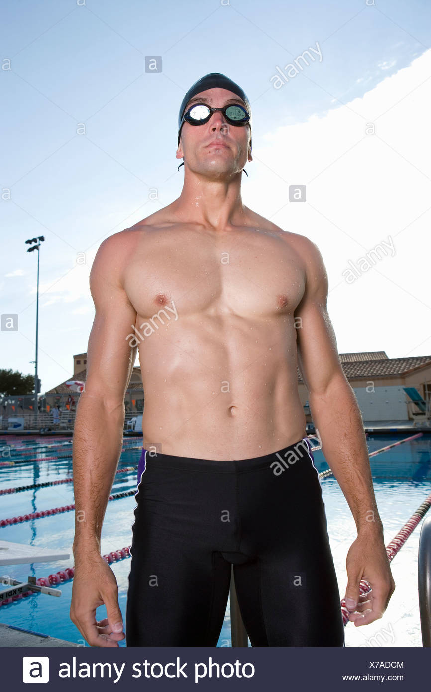 Young man in goggles and swim trunks next to swimming pool - Stock Image