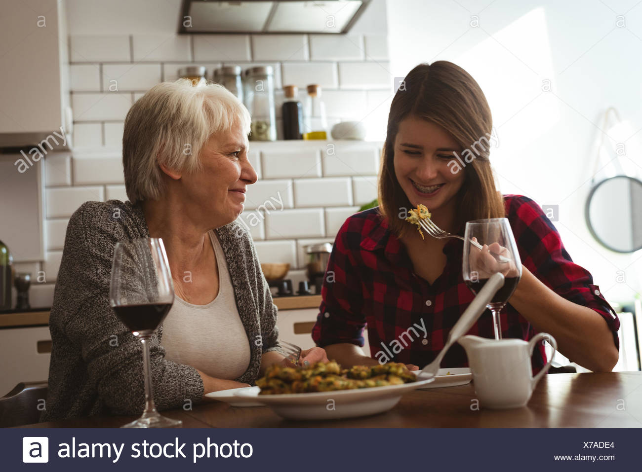 Senior woman and daughter eating omelet and wine - Stock Image