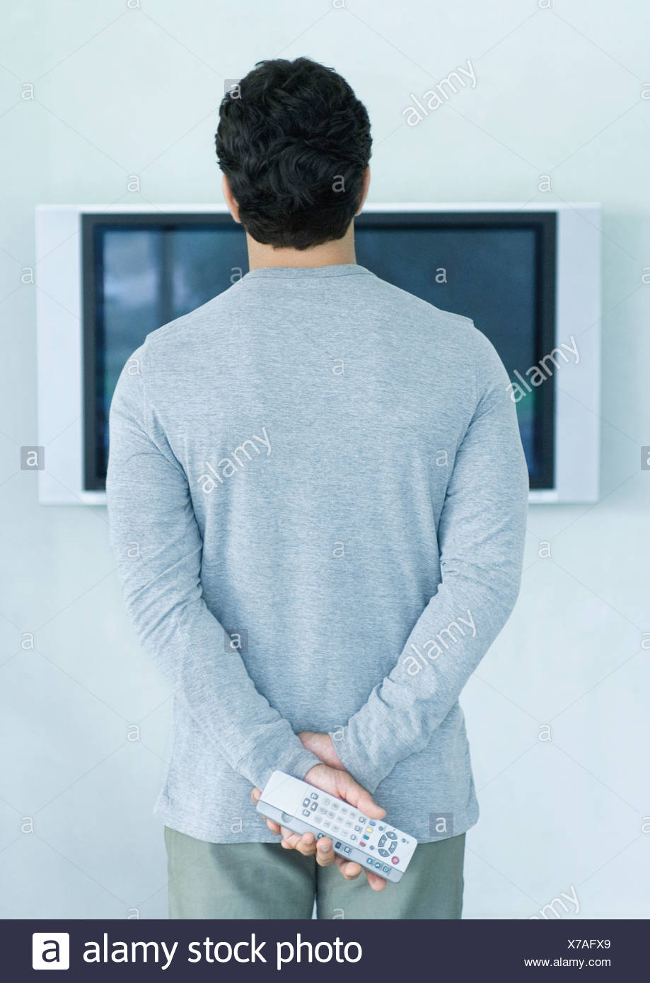 Man standing in front of widescreen TV, holding two remote controls, rear view - Stock Image