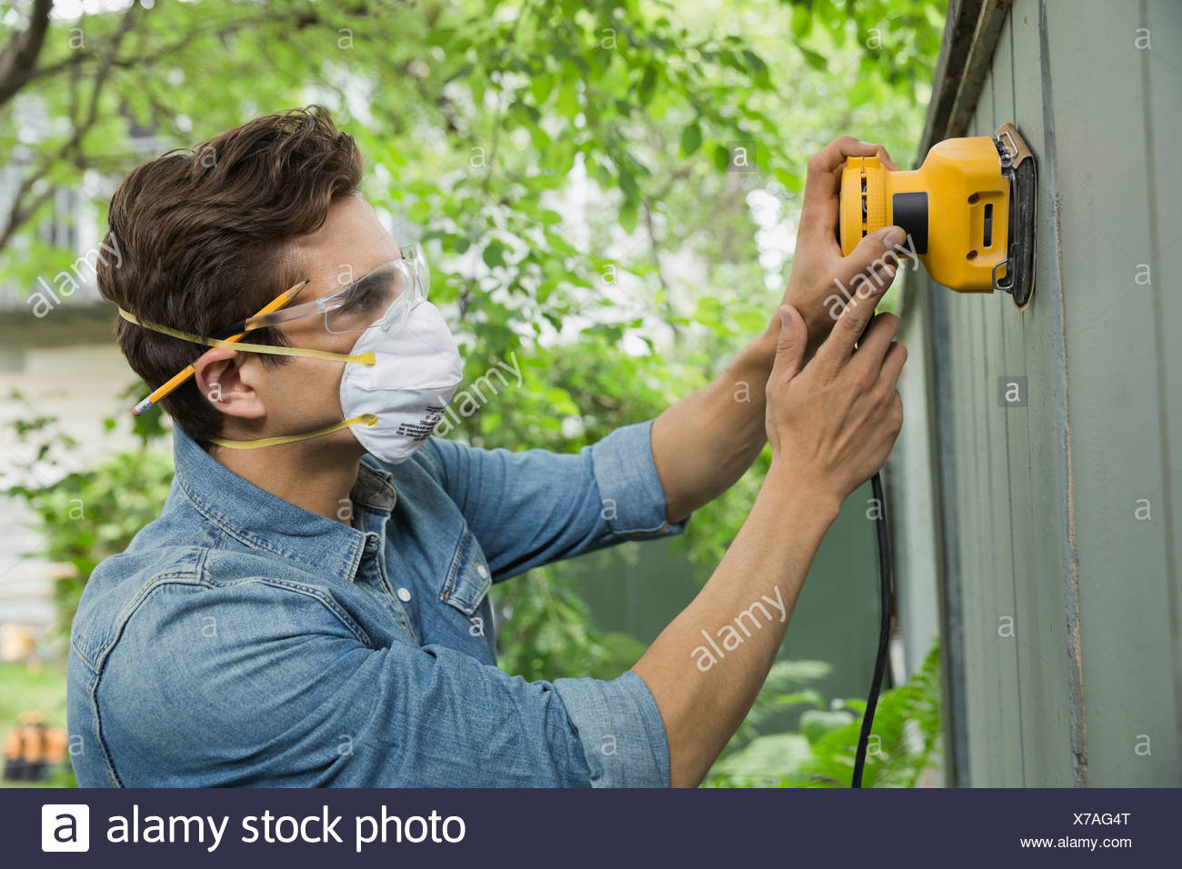 Man sanding down fench planks - Stock Image