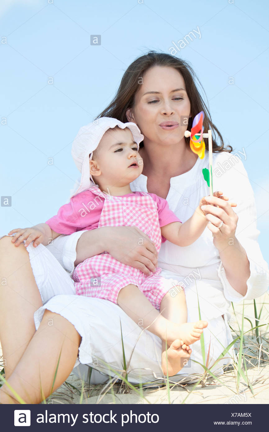 VÌ SAO NHO ? ......HÁT  - Page 5 Germany-bavaria-mother-blowing-paper-windmill-with-baby-girl-sitting-on-her-lap-X7AM5X