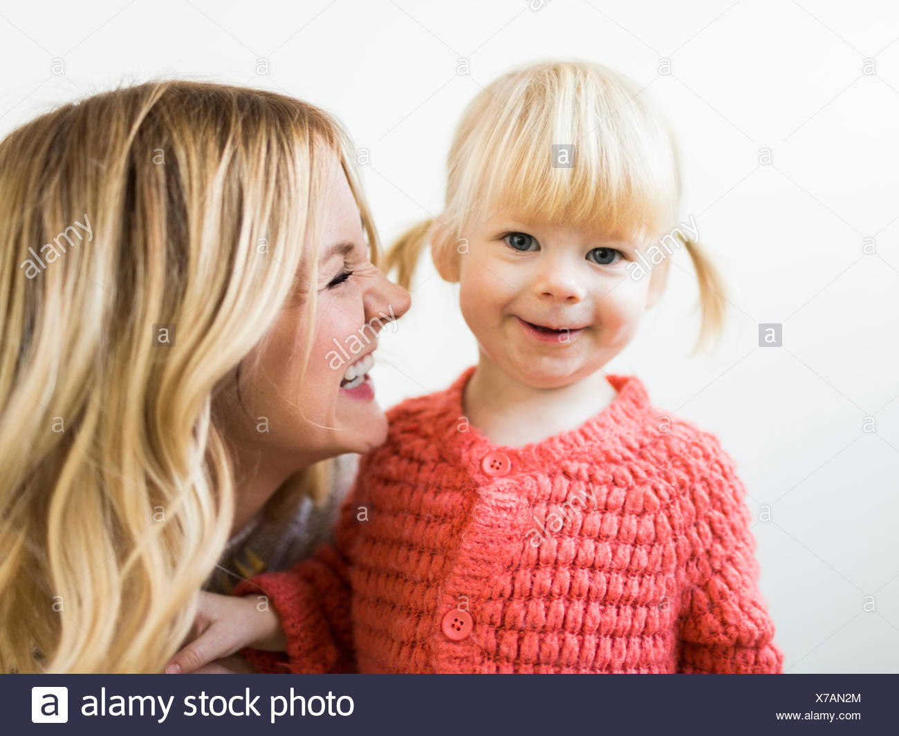 Cute girl (2-3) smiling at camera with mother - Stock Image