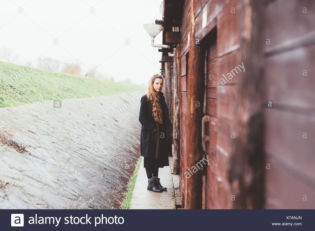 Portrait of young woman by weathered hut - Stock Image