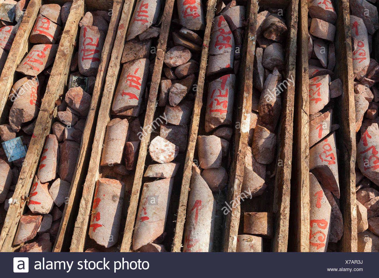 Labeled bedrock core samples collected by a drill rig from the bed of the Nam Ou River at the planned site for Dam #7 in Phou Den Din National Protected Area, Laos. - Stock Image