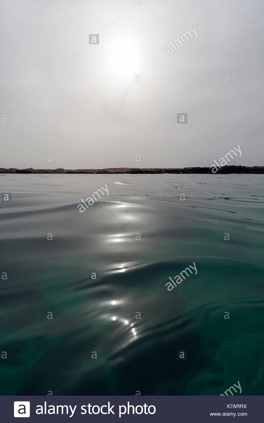 A faint sun pierces a grey sky over a calm ocean surface in the Gulf of Oman. - Stock Image