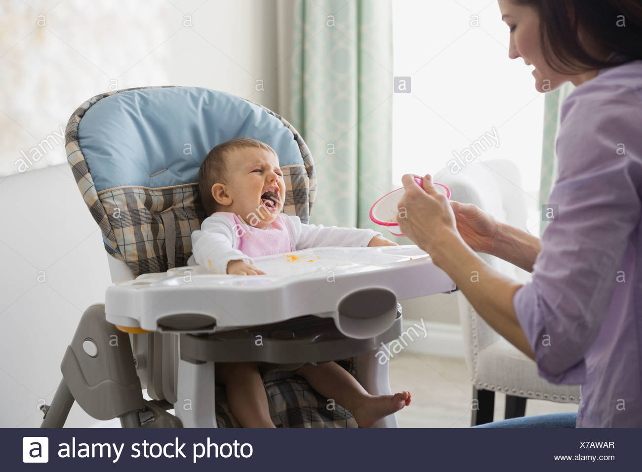Mother feeding crying baby at home - Stock Image