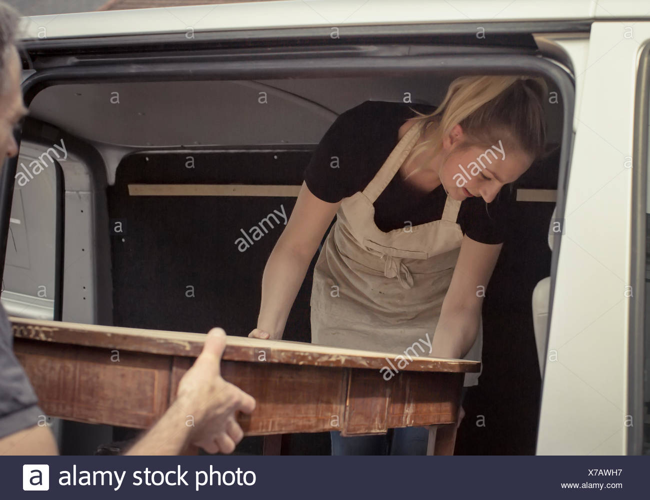 Two people, a man and a young woman lifting an antique wooden table into the back of a van. - Stock Image