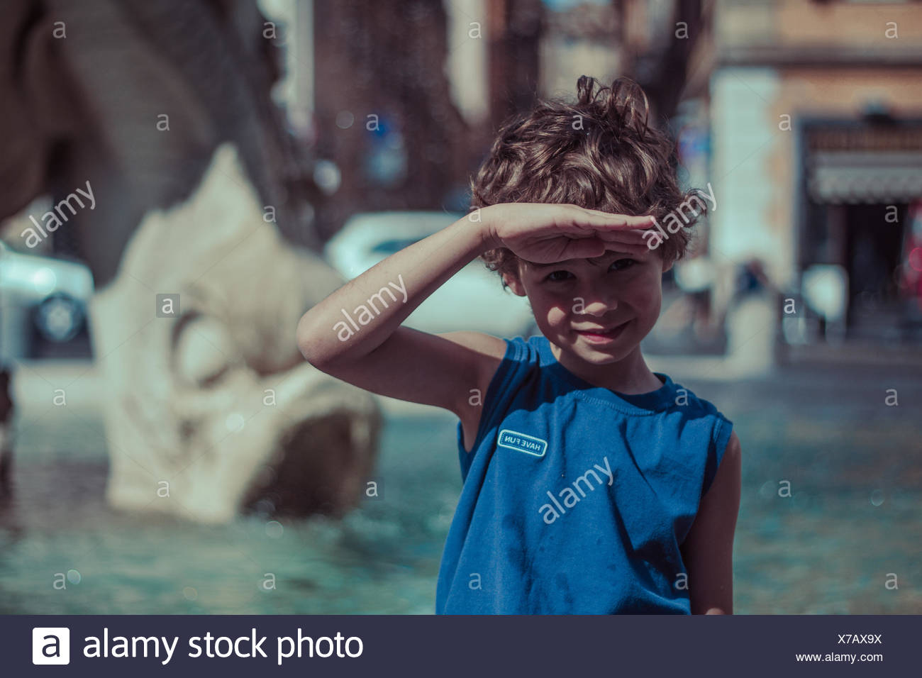 Boy looking at view with hand raised to forehead, shielding eyes - Stock Image